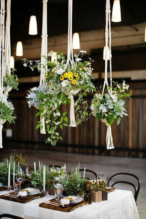 greenery and flowers in pots and macrame hangings over the tables