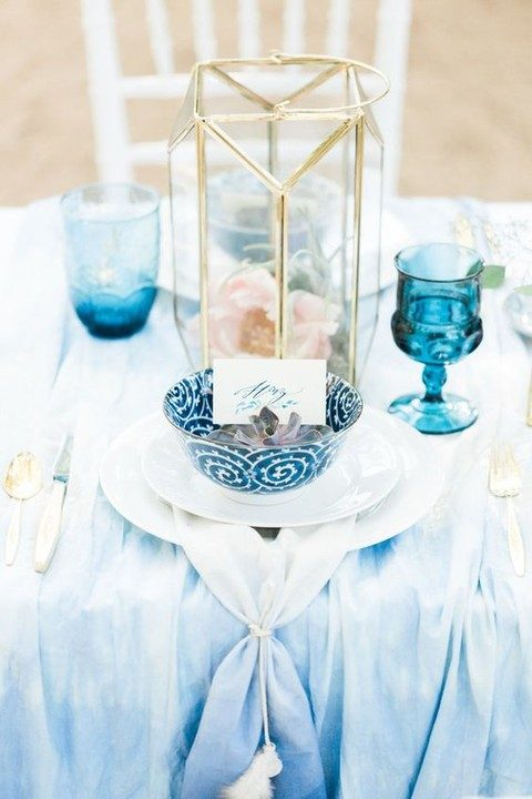 indigo-dyed tablecloth, a printed plate and colored glasses