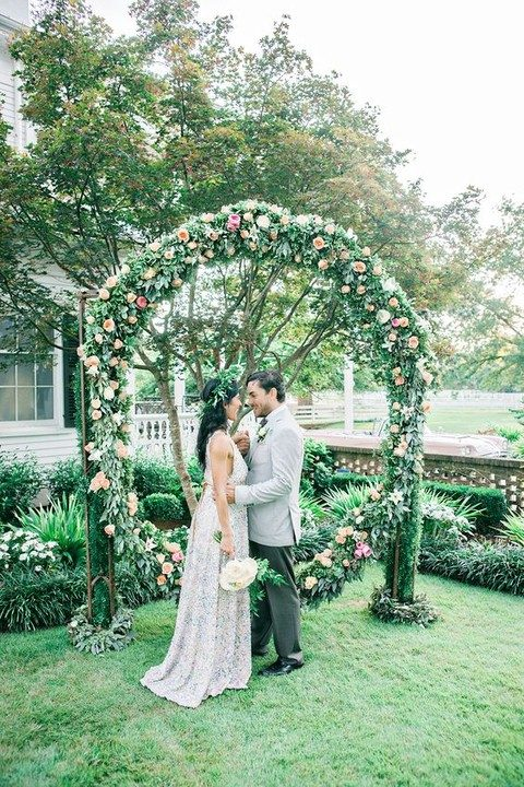 oversized green wreath placed on pillars with blush, pink and peachy blooms