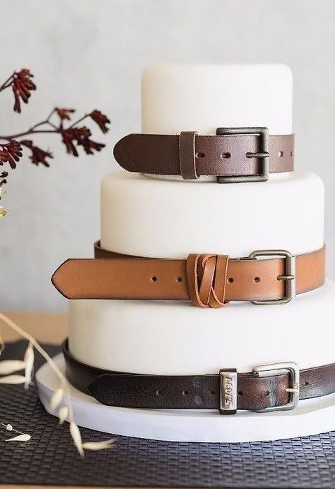 white fondant wedding cake with brown leather belts