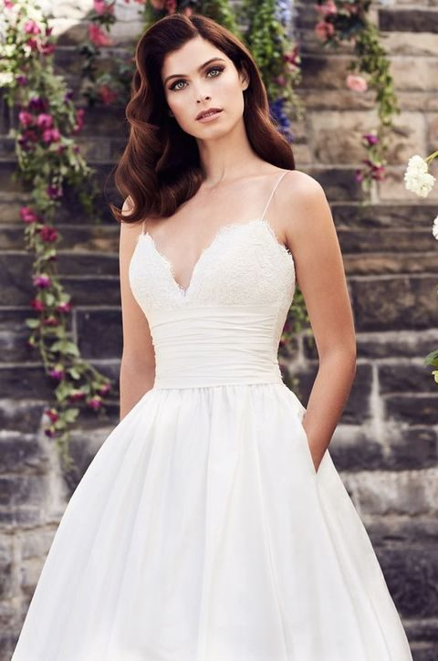 V-neck spaghetti strap wedding dress with side pockets on a plain skirt