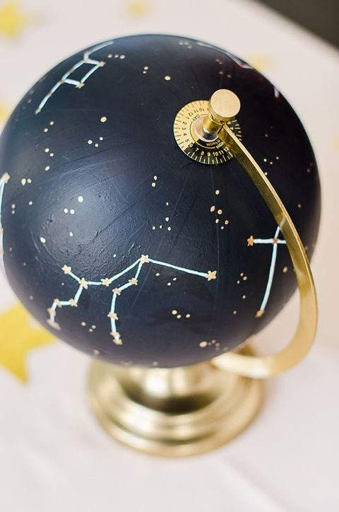 a navy globe with metallic constellations to use as a wedding centerpiece