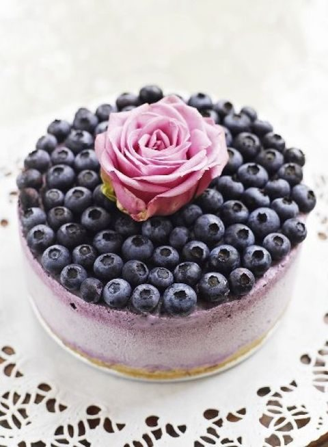 blue berry ice cream wedding cake topped with berries and a single bloom