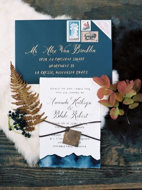 blue watercolor invitations with calligraphy and an antler tag