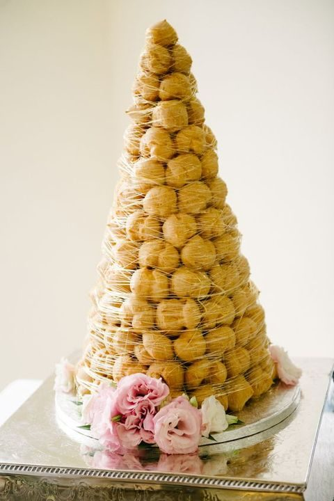 classic croquembouche covered with caramel and served wtih fresh blooms