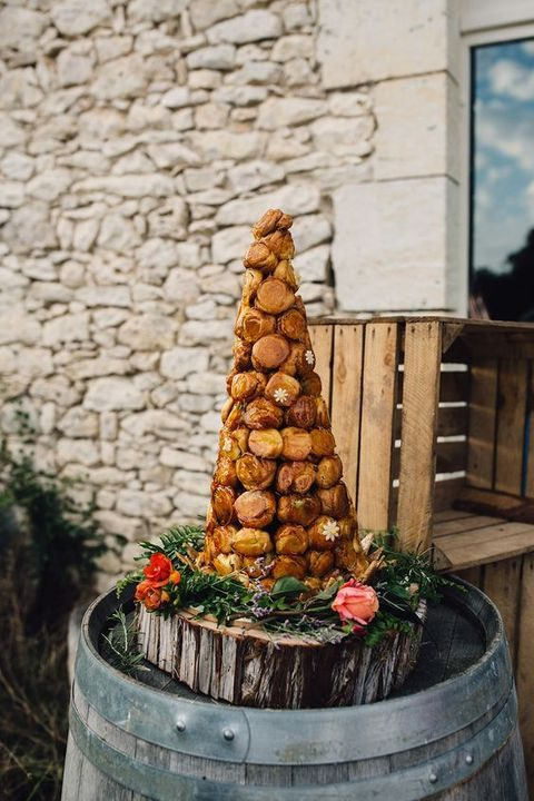 croquembouche served on a wooden slice with foliage and flowers
