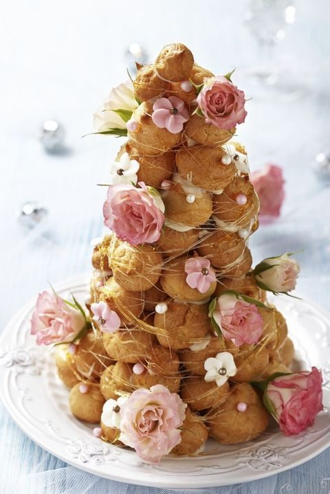croquembouche with caramel threads, fresh pink roses and edible beads and flowers