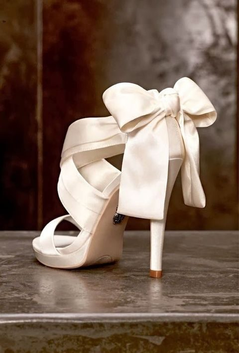 cutout white wedding shoes with large bows on the back
