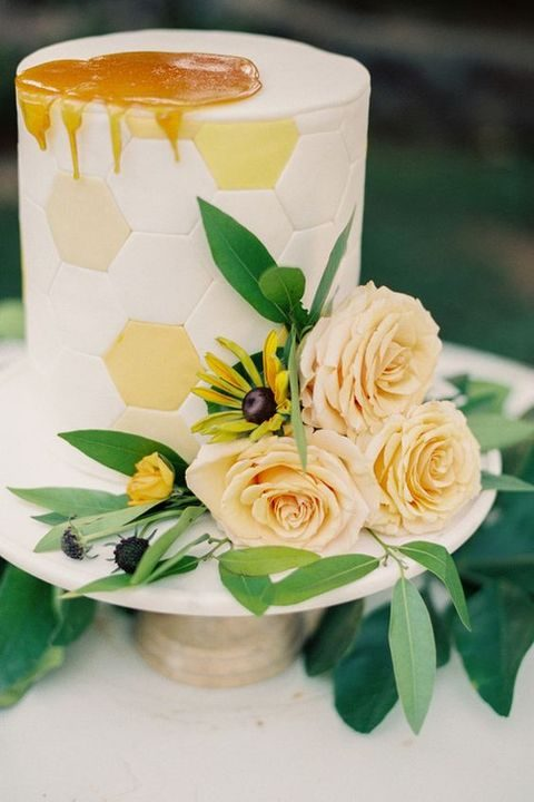 honeycomb wedding cake displayed with flowers and topped with honey