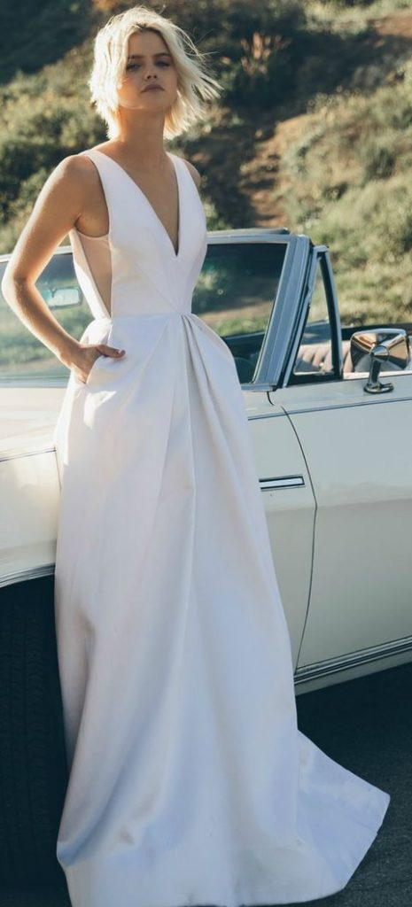 low back plunging neckline wedding dress with pockets made from couture silk with hand pleated panels