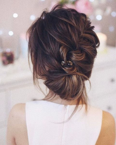 messy diagonal braid with a rhinestone hairpin