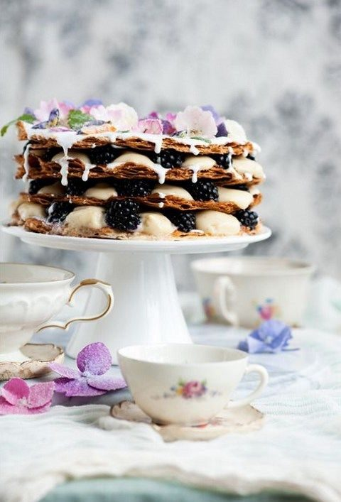 millefoglie wedding cake with vanilla cream and blackberries, topped with petals