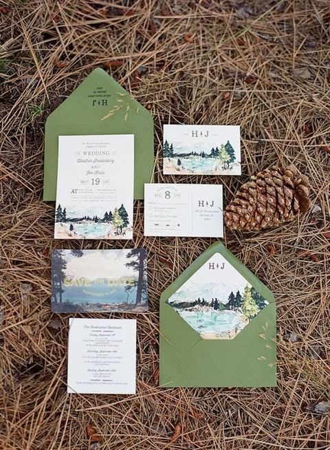 sage green envelopes with watercolor landscapes on the invites