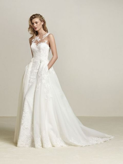 sleeveless illusion neckline lace applique wedding dress with an overskirt with pockets by Pronovias