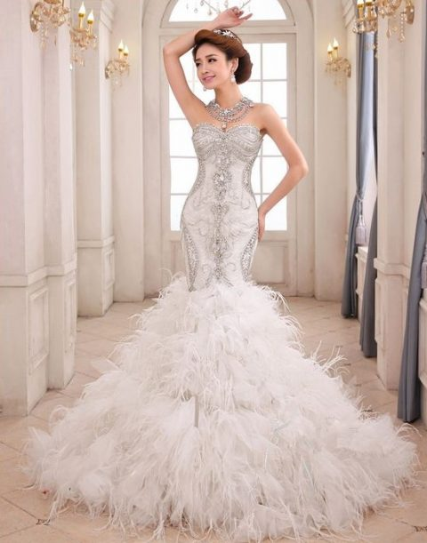 strapless heavily embellished mermaid wedding dress with a feather skirt