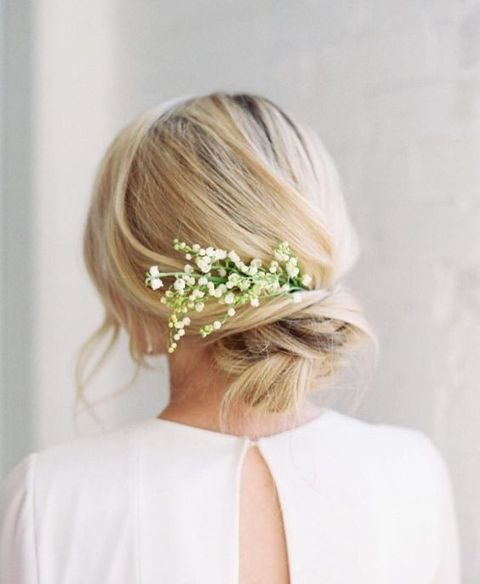 twisted low bun with lily of the valley tucked in