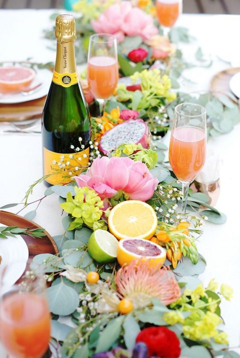 a bold table runner with leaves, tropical flowers, citrus and fruits for a tropical wedding