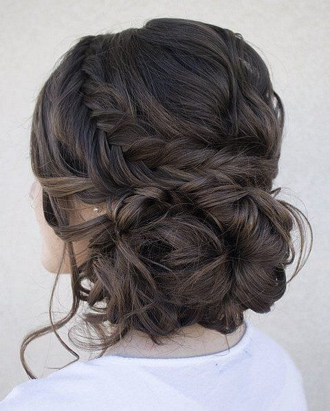 a braided messy updo with a messy low bun and some locks down