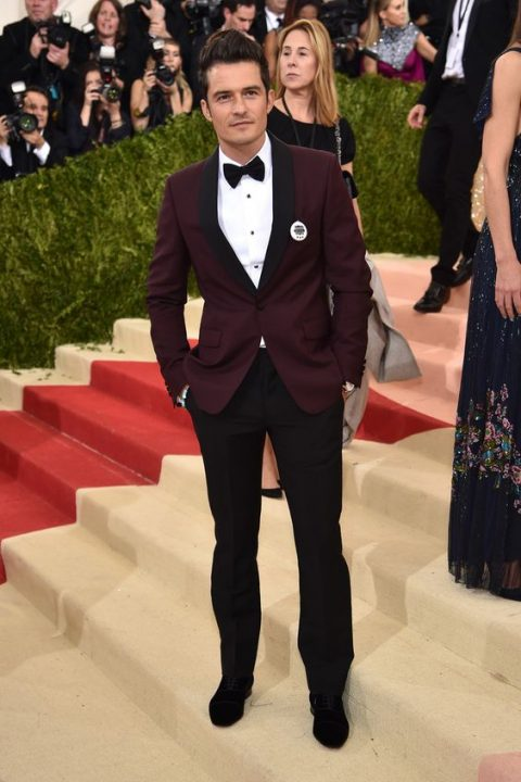 a burgundy dinner jacket with black lapels and black trousers and a bow tie