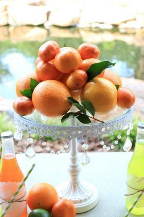 a crystal stand with oranges and tangerines for a tropical celebration