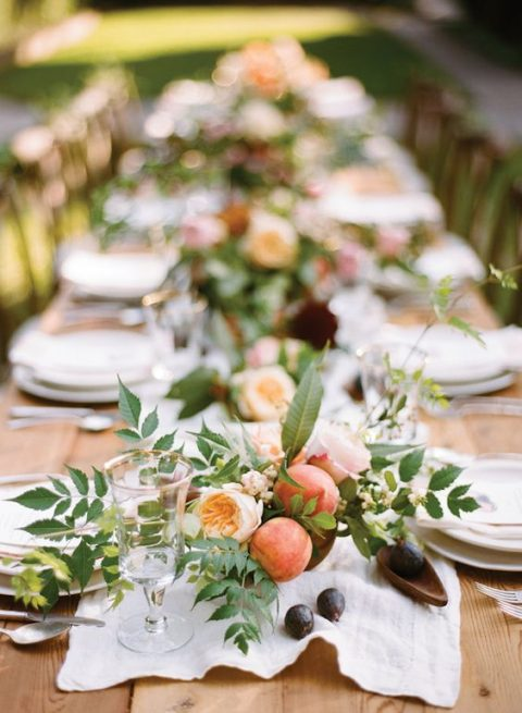 a cute centerpiece with peaches, ivory blooms and greenery for a rustic tablescape