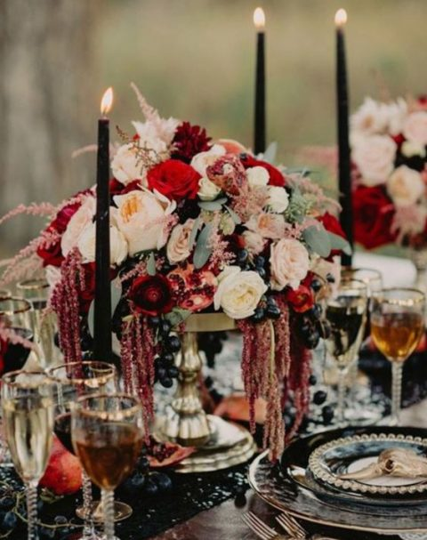 a decadent centerpiece with red and blush blooms and grapes