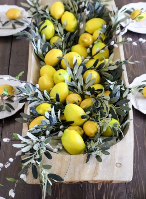 a dough bowl with willow pussy branches and lemons for tropical or summer wedding