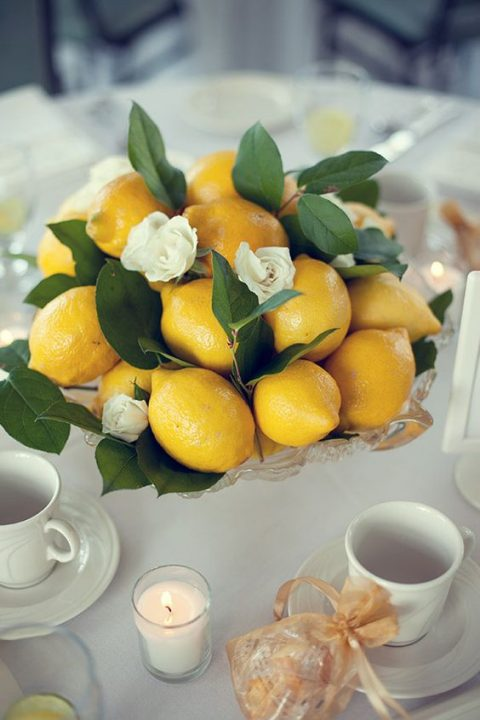 a glass bowl with lemons, leaves and white roses for a summer wedding
