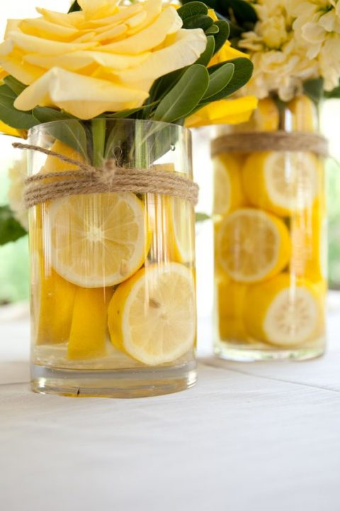 a glass with lemon slices, yellow roses and covered with twine
