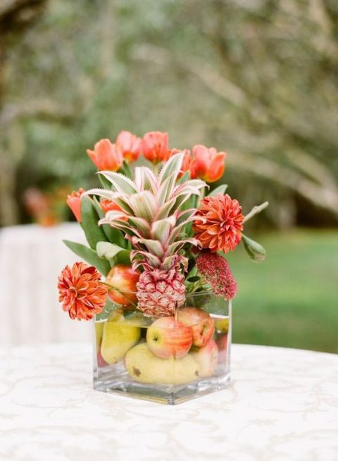 a glass with pears, apples, pineapples and orange blooms