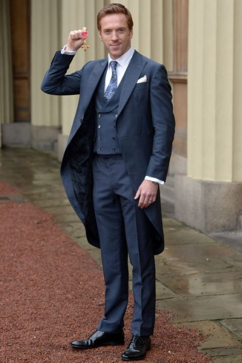 a graphite grey morning suit with a white shirt and a blue printed tie worn by Damian Lewis