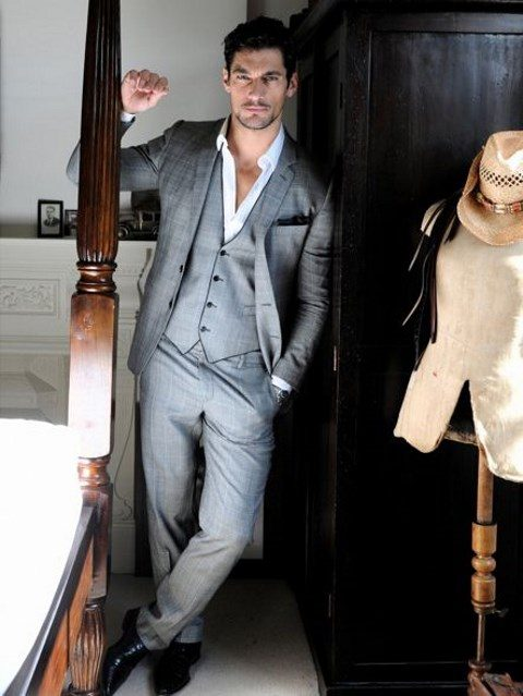 a grey three piece wedding suit with a black edge vest and a white shirt, no tie