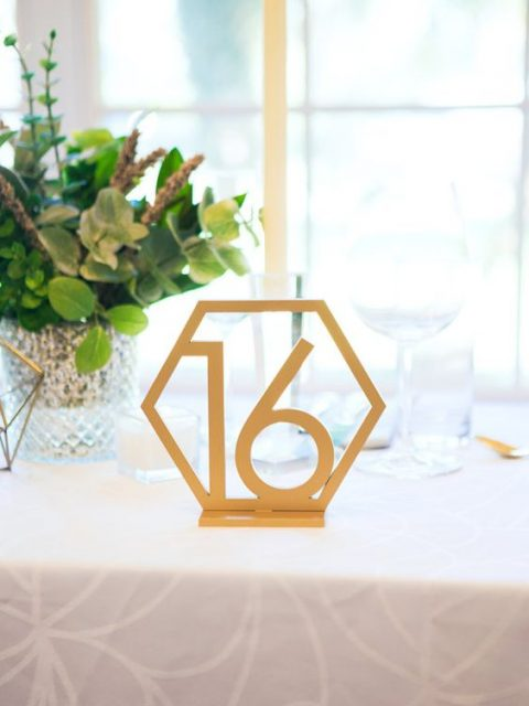 a hexagon shaped table number painted gold