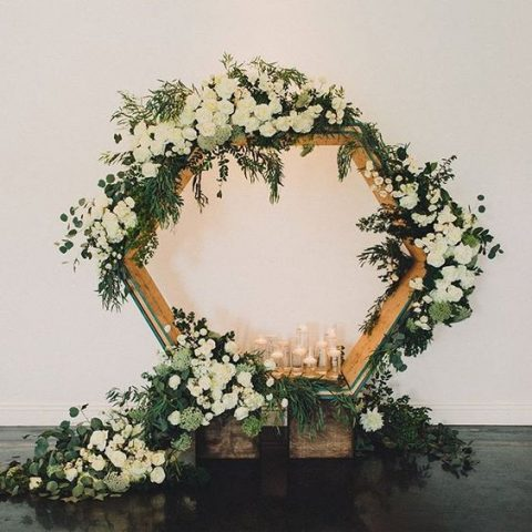 a large hexagon, greenery and lush florals wedding backdrop with candles