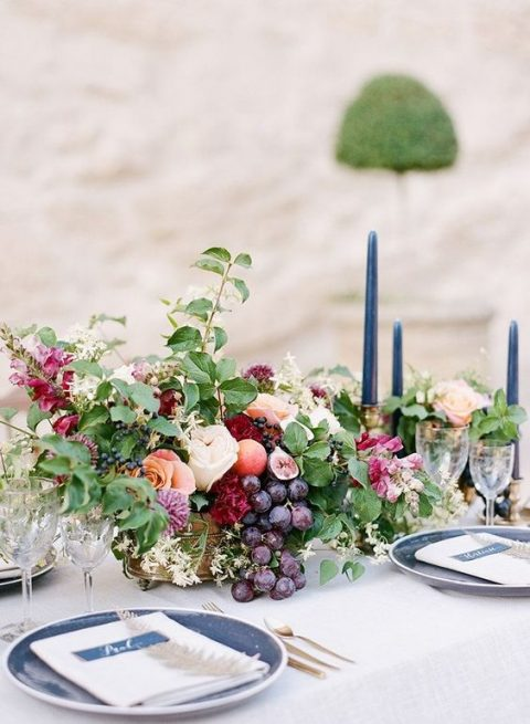 a lush centerpiece with grapes, figs, peaches and greeenery and pastel flowers