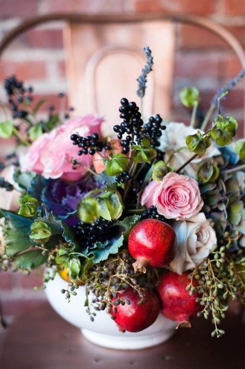 a lush centerpiece with pink blooms, greenery and pomegranates for a fall or summer wedding