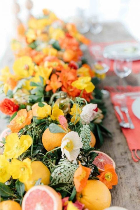 a lush table runner with red and orange flowers and citrus for a summer wedding