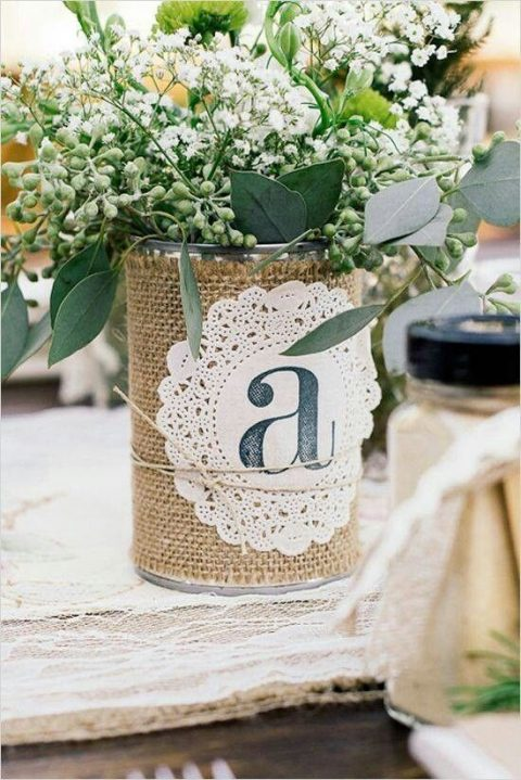a metal tin can wrapped in burlap and a paper doily with a table name