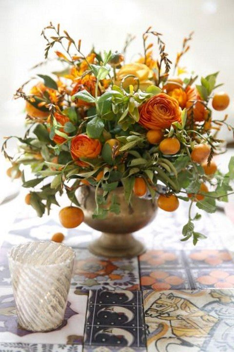 a metal urn with orange blooms, greenery and kumquats