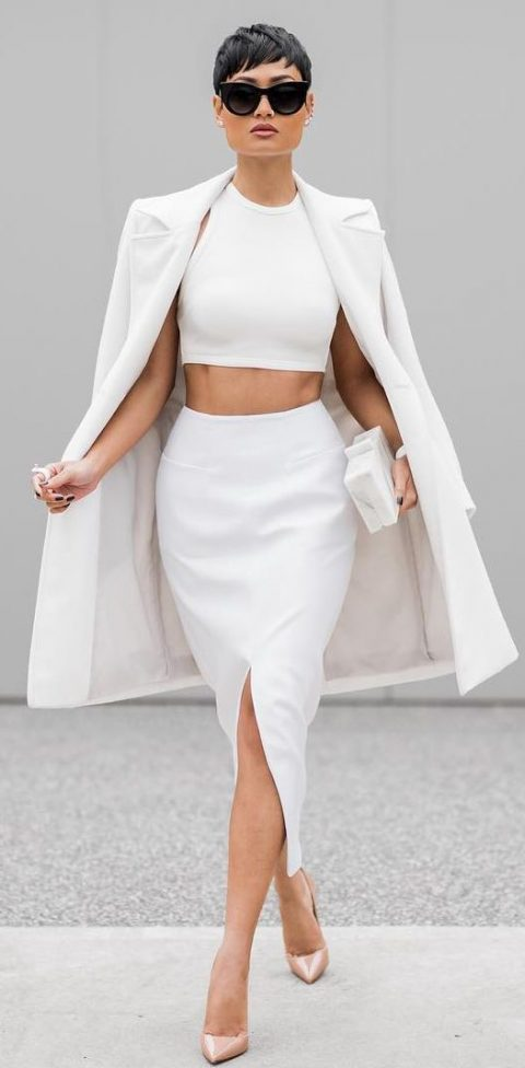a minimalist white separate with a halter neckline crop top and a pencil slit skirt, a white coat