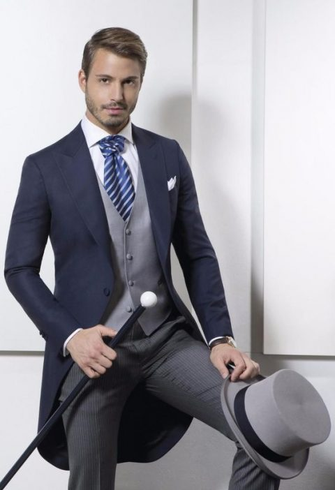 a morning suit with striped pants, a navy jacket, a grey vest and a blue striped tie