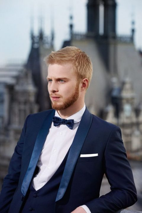 a navy dinner jacket with shiny blue lapels, a shiny bow tie and a vest