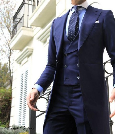 a navy morning suit with a navy polka dot tie