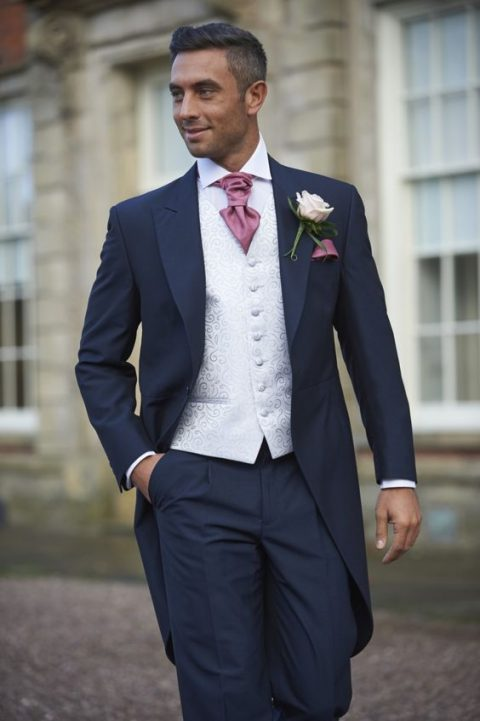 a navy morning suit with a white patterned vest and a pink tie