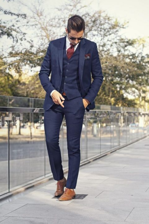 A Navy Three Piece Wedding Suit With Striped Burgundy Tie And Brown Shoes