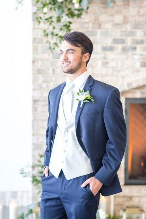 a navy three piece wedding suit with a white vest, shirt and tie