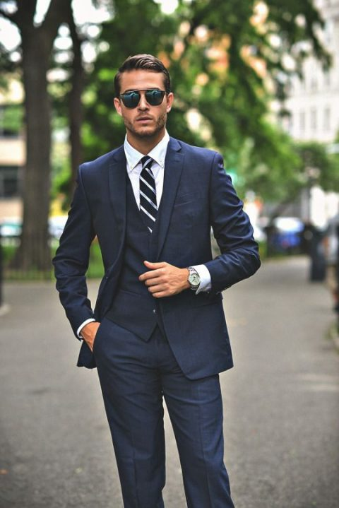 a navy three piece wedidng suit with a white shirt and a striped tie
