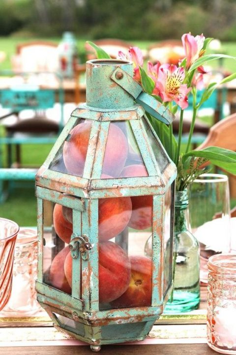 a patina and glass lantern with peaches inside