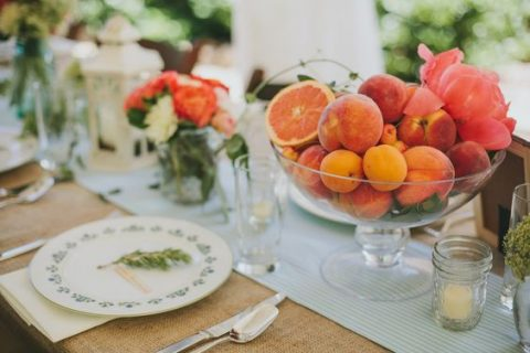 a summer centerpiece of a glass bowl withpeaches, apricots and citrus and a bold bloom