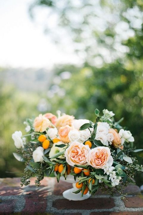 a summer centerpiece with blush and ivory blooms and kumquats